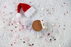 Julfotografibild med drink- och kortkortmarshmallower för varm choklad som formas som snögubben som läggas i snö med jultomtenhat royaltyfri fotografi