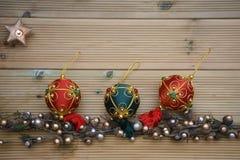 Julfotografibild med silver och guld färgade ekollonträdgarneringar på naturlig lantlig wood bakgrund med den tända stearinljuset royaltyfria bilder