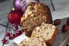 Julfruktkaka med mutter- och julgarneringar på träbräde Royaltyfria Foton