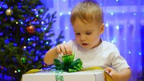Julgåvaöverraskning - ett barn öppnar gåva Royaltyfri Fotografi