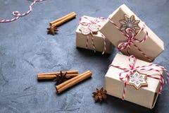 Julgåva eller närvarande ask som slås in i kraft papper med garnering på den mörka tabellen Gåva som dekoreras med julkakor fotografering för bildbyråer