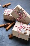Julgåva eller närvarande ask som slås in i kraft papper med garnering på den mörka tabellen Gåva som dekoreras med julkakor arkivfoton