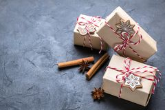 Julgåva eller närvarande ask som slås in i kraft papper med garnering på den mörka tabellen Gåva som dekoreras med julkakor royaltyfri bild
