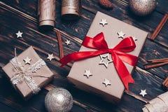 Julgåva eller närvarande ask som slås in i kraft papper med garnering på lantlig bakgrund från över lekmanna- stil för lägenhet arkivbilder