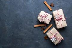 Julgåva eller närvarande ask som slås in i kraft papper med garnering på mörk bakgrund Gåva som dekoreras med julkakor royaltyfri fotografi