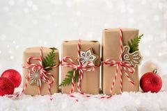 Julgåva eller närvarande ask som slås in i kraft papper med garnering på vit bakgrund arkivfoton