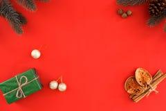 Julgåva, gransidor och Xmas-garnering på röd bakgrund arkivfoto