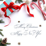 Julgåva, granträdfilialer och julprydnad på whit Royaltyfri Foto