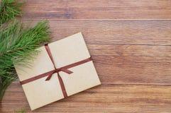 Julgåva i en kraft ask med bandet på en brun träbakgrund P royaltyfri bild