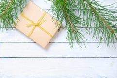 Julgåva i en kraft ask och en prydlig filial På en vit träbakgrund arkivfoton