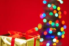 Julgåva med trädet och röd bakgrund Fotografering för Bildbyråer