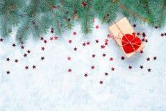 Julgåva på bakgrunden av julgranfilialer som dekoreras med hjärtor royaltyfri bild