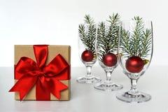 Julgåva som binds med det röda bandet och julbollar Royaltyfri Fotografi