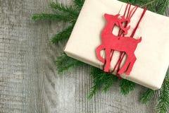 Julgåvaask med den röda renen som leksak- och granträd på träbräde Top beskådar Royaltyfria Bilder