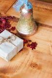 Julgåvaask och guld- klirrklocka på träbakgrund letters amerikansk för färgexplosionen för kortet 3d ferie för hälsningen för fla Royaltyfria Bilder