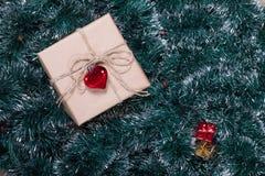 Julgåvaask på enträd och girlandbakgrund Gåvor för förpackande ferie Royaltyfri Bild