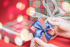 Julgåvaask på röd bakgrund med den magiska ljusstjärnan Royaltyfri Foto