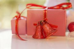 Julgåvaask, röd klirrklocka och suddigt granträd mot royaltyfri bild