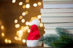 Julgåvaask, Santa Claus hatt och hög av böcker Arkivfoto