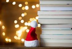 Julgåvaask, Santa Claus hatt och hög av böcker Royaltyfria Bilder