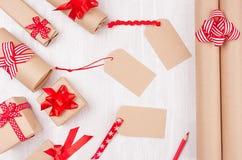 Julgåvaaskar av kraft papper med röda pilbågar och bandet och tomma etiketter på mjukt vitt träbräde royaltyfri bild