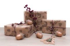 Julgåvaaskar i brunt hantverkpapper med julexponeringsglasleksaker royaltyfria foton