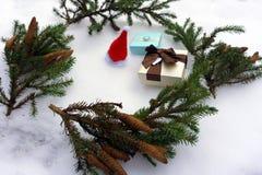 Julgåvaaskar i filialer för kraft papper och granpå snö-täckt bakgrund royaltyfri bild