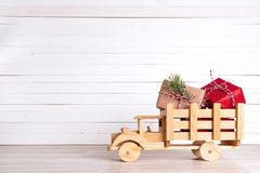 Julgåvaaskar i träleksak åker lastbil på den vita träbackgroen Arkivbild