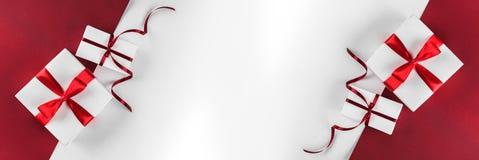 Julgåvaaskar med det röda bandet, garnering på vit och röd pappers- bakgrund Tema för Xmas och för lyckligt nytt år arkivfoton