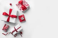 Julgåvaaskar med det röda bandet och garnering på vit bakgrund royaltyfria bilder
