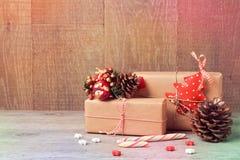 Julgåvaaskar med godisen på trätabellen royaltyfri bild