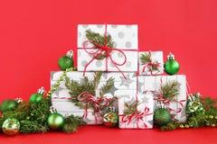 Julgåvaaskar på en röd bakgrund som dekoreras av granfilialer, sörjer kottar och skinande grönt julpynt royaltyfria foton