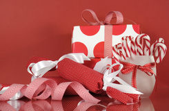 Julgåvaaskar på röd bakgrund, med bandgodisrottingar och smällare Arkivfoton