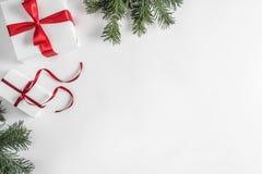 Julgåvaaskar på vit bakgrund med granfilialer, sörjer kottar, röd garnering royaltyfri bild
