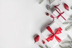 Julgåvaaskar på vit bakgrund med granfilialer, sörjer kottar, röd garnering arkivfoton