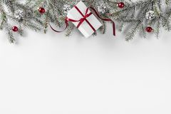 Julgåvaaskar på vit bakgrund med granfilialer, sörjer kottar, rött band arkivfoto