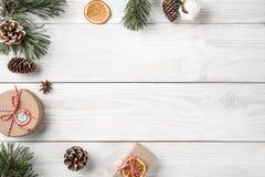 Julgåvaaskar på vit träbakgrund med granfilialer, sörjer kottar royaltyfri fotografi
