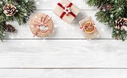 Julgåvaaskar på vit träbakgrund med granfilialer, sörjer kottar arkivbilder