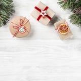 Julgåvaaskar på vit träbakgrund med granfilialer, sörjer kottar Tema för Xmas och för lyckligt nytt år fotografering för bildbyråer