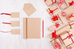 Julgåvaaskar, tomma etiketter och notepad för din text av kraft papper med röda pilbågar och bandet på mjukt vitt träbräde royaltyfri foto