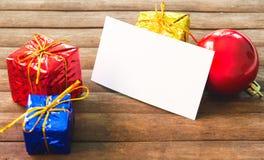 Julgåvadekor och tomt pappers- kort på trätabellen Julkortmodell Royaltyfri Fotografi