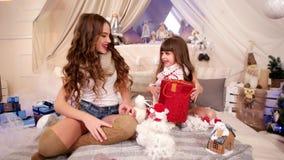 Julgåvan, det lyckliga barnet är jubilantly överraskningen, familj firar det nya året, förtjusande systerutbytesgåvor stock video