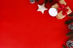 Julgåvan, gransidor, sörjer kotten och stjärnan på röd bakgrund fotografering för bildbyråer