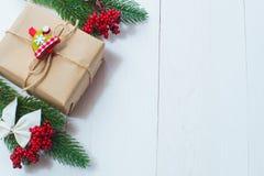 Julgåvan och en kvist av sörjer visare på en vit bakgrund Arkivfoton