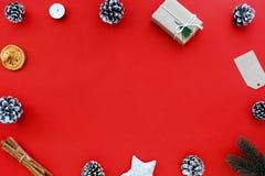 Julgåvan, sörjer kotten och Xmas-garnering på röd bakgrund royaltyfria bilder