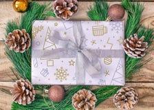 Julgåvasjal, gåvapapper, gåvaaskar, granträd, med kottar och garneringar på en träbakgrund fotografering för bildbyråer