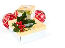 Julgåvor, baubles och järnek Arkivbilder