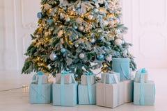 Julgåvor i askar under träd, slut upp arkivfoto