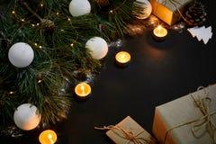 Julgåvor, julträdet, stearinljus, den kulöra dekoren, stjärnor, klumpa ihop sig på svart bakgrund Royaltyfri Fotografi