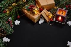 Julgåvor, julträdet, stearinljus, den kulöra dekoren, stjärnor, klumpa ihop sig på svart bakgrund Royaltyfria Foton